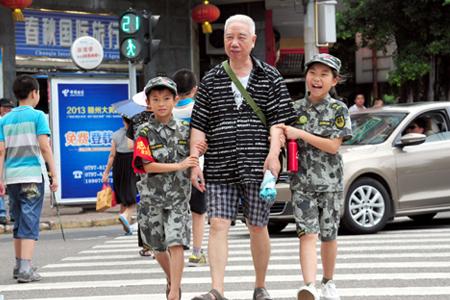 学生志愿者在赣州市厚德路护送行人过斑马线.jpg