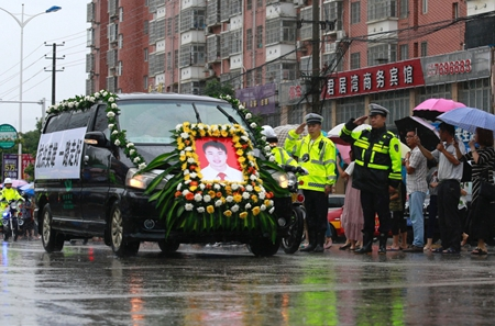 维持秩序的交警向经过的程扶摇送别车队敬礼(6月30日)。新华社记者黄喆.jpg