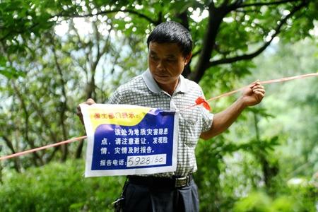 7月3日,广西融水苗族自治县龙培村党支部书记杨优寿在设置告示牌,提醒人们不要进入山体塌方危险区域。 新华社记者张爱林 摄